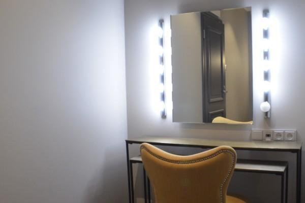 En stol och en spegel med lampor.