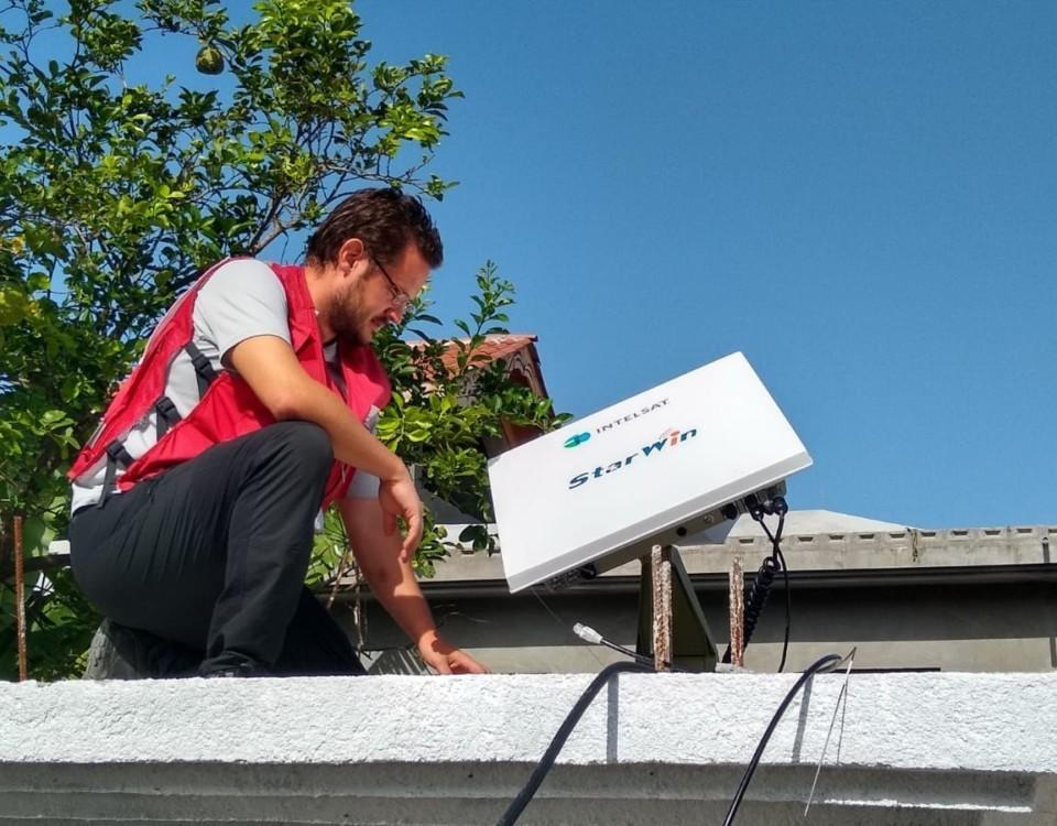 Man jobbar med teknisk utrustning på ett tak. PÅ sig har han en röd väst