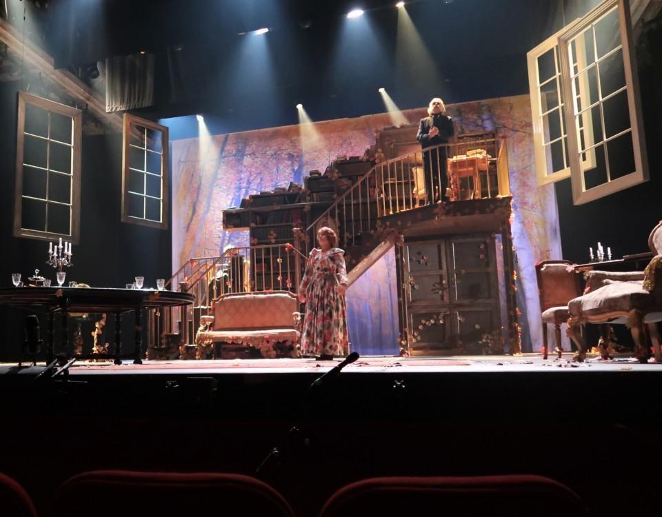 Bild av teaterscen. En kvinna i blommig klänning och en skäggig man på en trappa står på scennen.