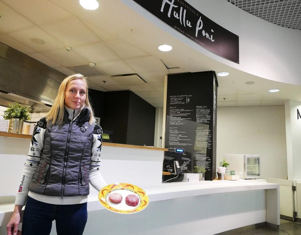 Kvinna med en tallrik i handen, som har två råa burgarbiffar. Kvinnan står framför restaurangen Hullu Poni, som finns i Guldhuset i Hansa.