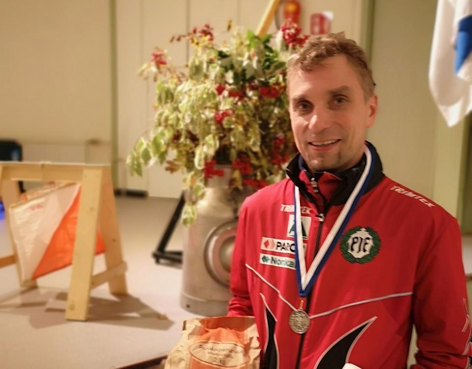 en man i idrottsoverall med en medalj