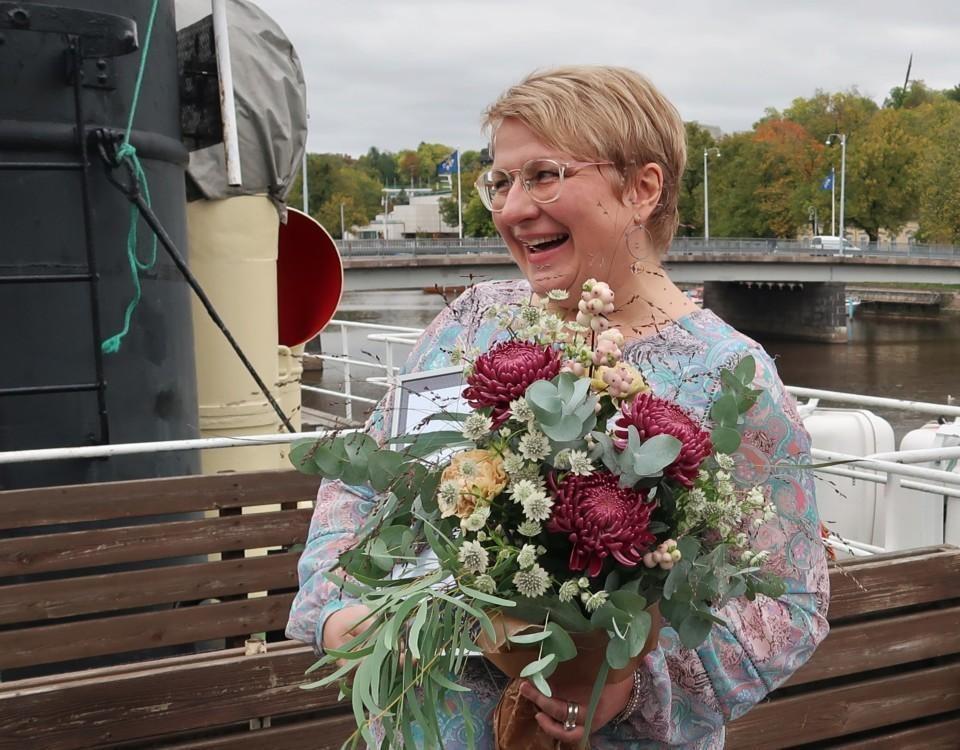 Porträtt av kvinna med glasögon som skrattar och ser snett förbi kameran och håller i en stor blombukett. I bakgrunden Aura å.