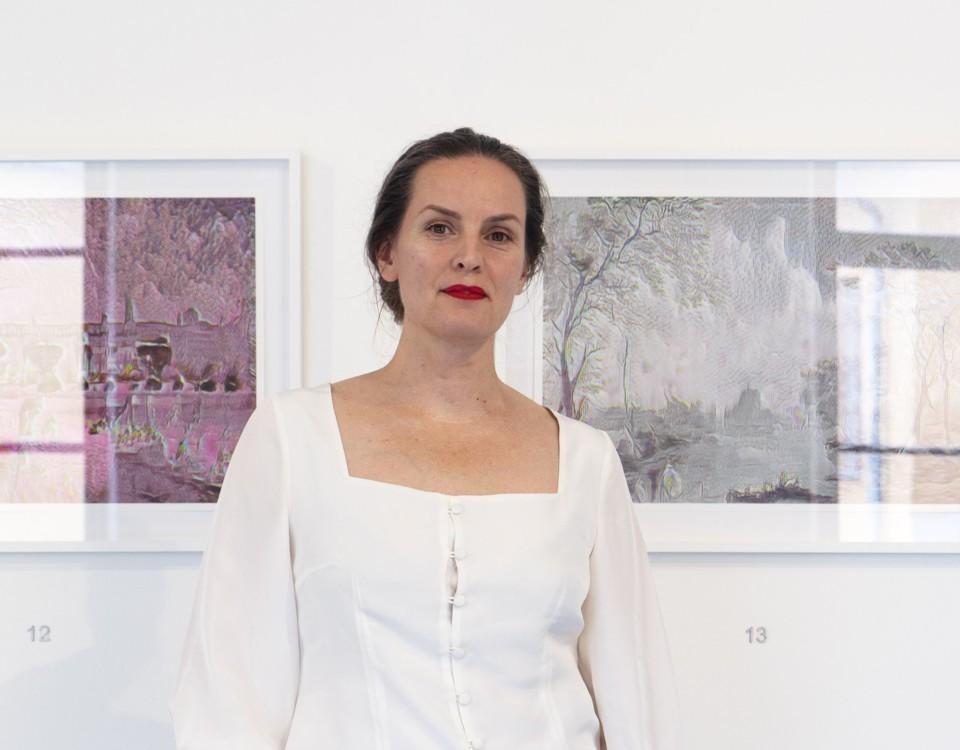 en kvinna i vitt framför tavlor