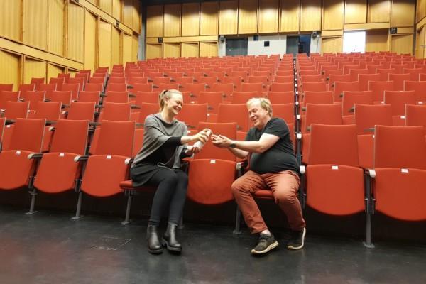 Man och kvinna använder handsprit i ett stort auditorium
