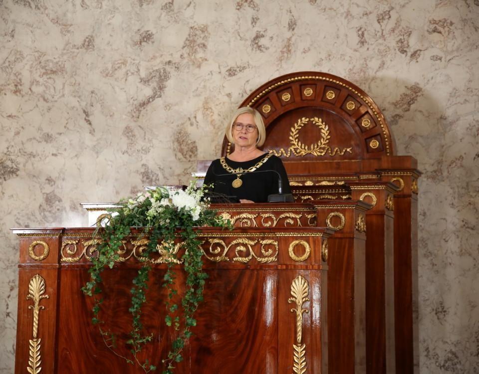 kvinna i ståtlig talarstol med förgyllningar