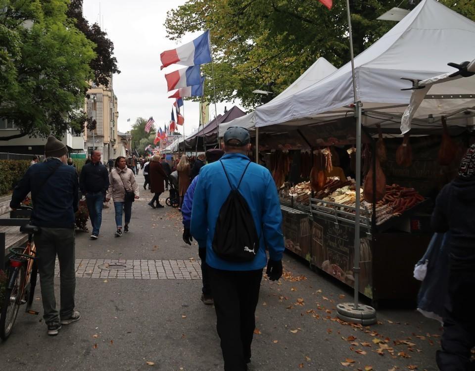 Bild av marknad. Flera franska flaggor syns på bilden. Männsikor går längs med stånden. Det är regnsjukt.