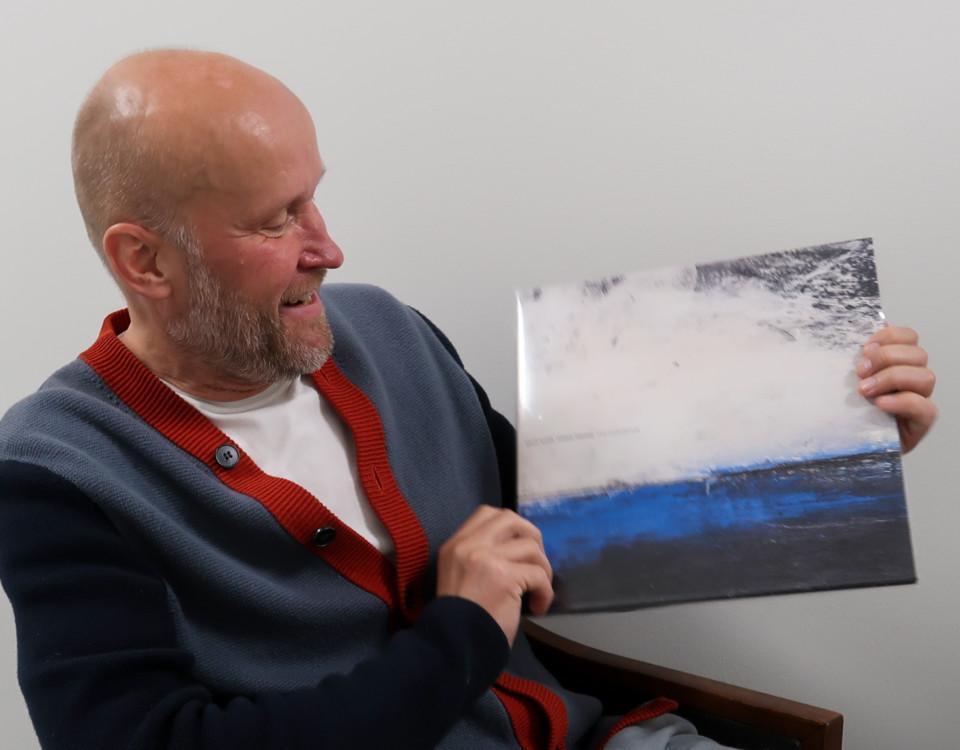 Porträtt av man som sitter och håller upp en vinylalbum som han tittar på. Albumets omslag föreställer en målning av ett hav.