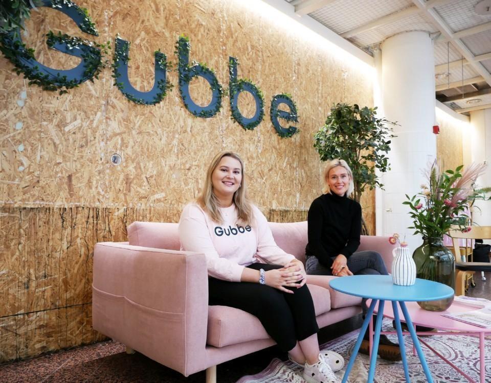 Asumalahti och Laaksonen sitter på en rosa soffa framför en stor Gubbe-logo.