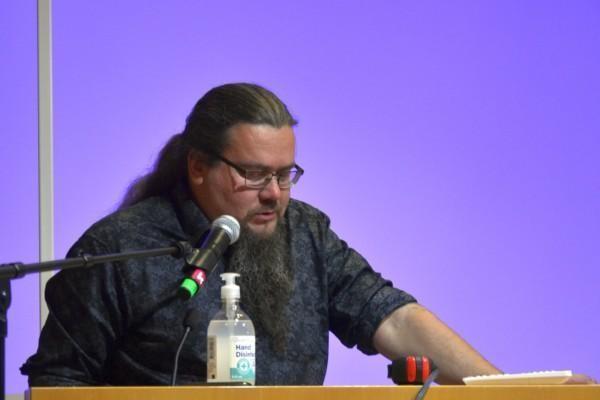 En man i långt mörkt hår och glasögon talar