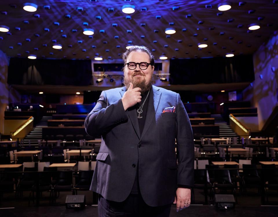 en man i runda glasögon i en sal