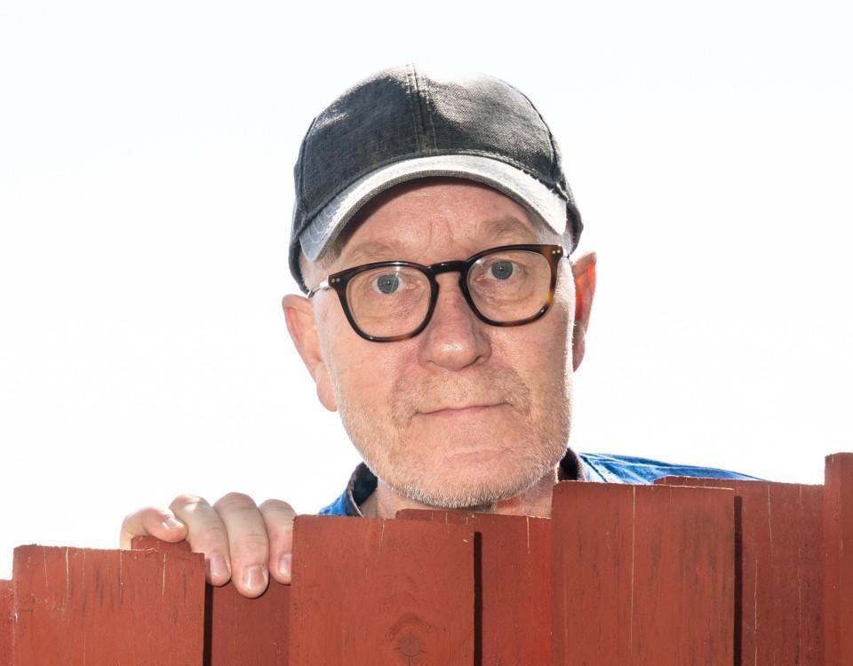 man med glasögon och keps tittar fram bakåt ett staket