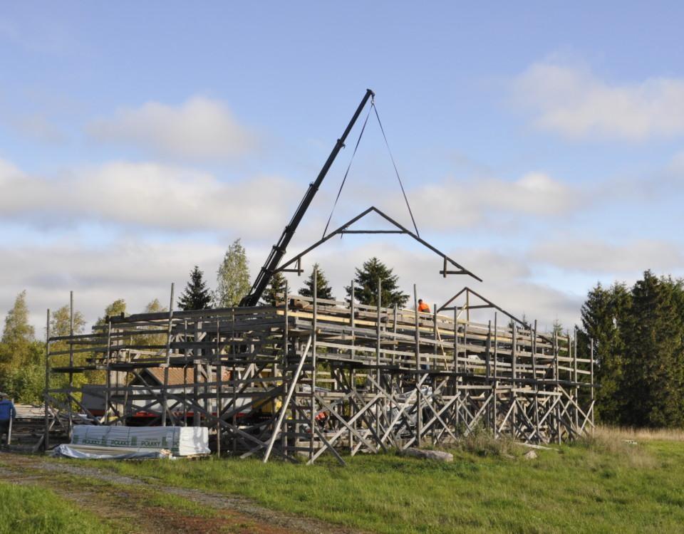 takstol lyfts på en byggnadsstomme i trä