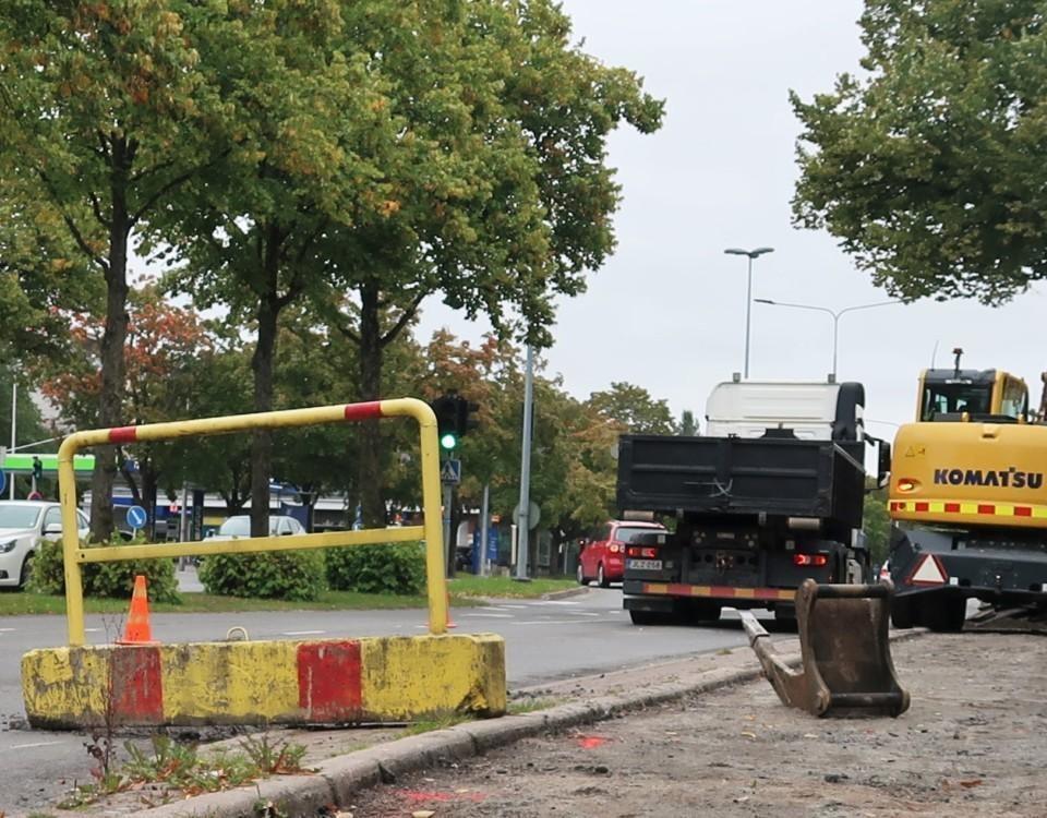 Bild av vägarbete vid tvåfilig enkelriktad väg. Den ena filen är avstängd och blockeras av av en betongspärr. I bakgrunden finns en lastbil och en grävskopa.