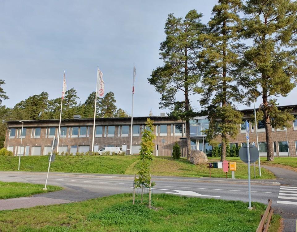 tvåvåningshus med flaggstänger framför och träd runt omkring