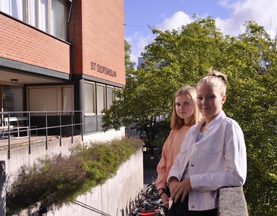 Två flickor står på en trappa