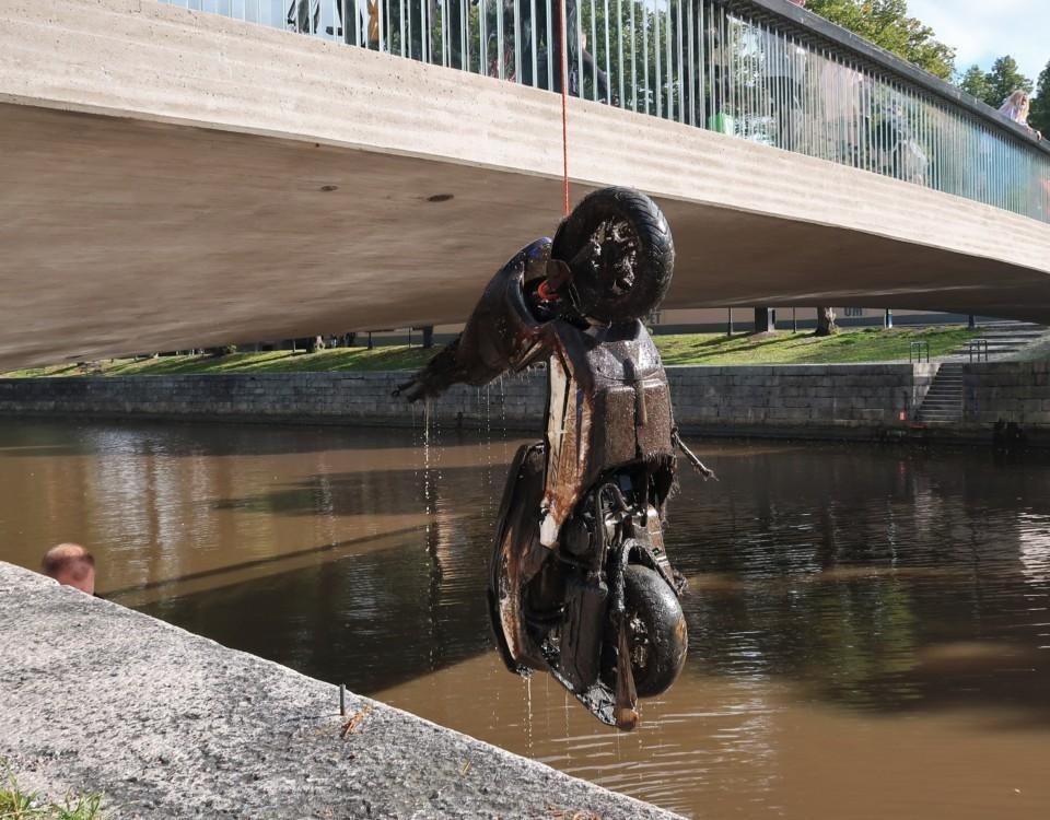 Moped som hänger från en lyftkran från framhjulet. Mopeden har precis hissats upp från Aura å och det droppar vatten från den.