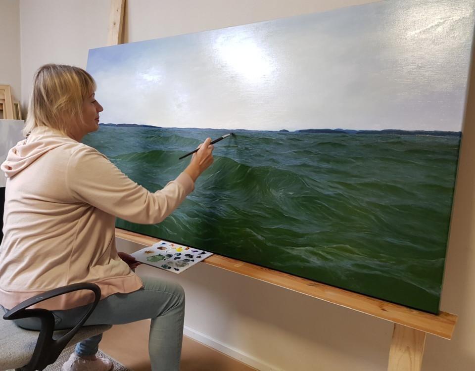 dam snett bakifrån. Hon målar på en stor tavla föreställande ett hav