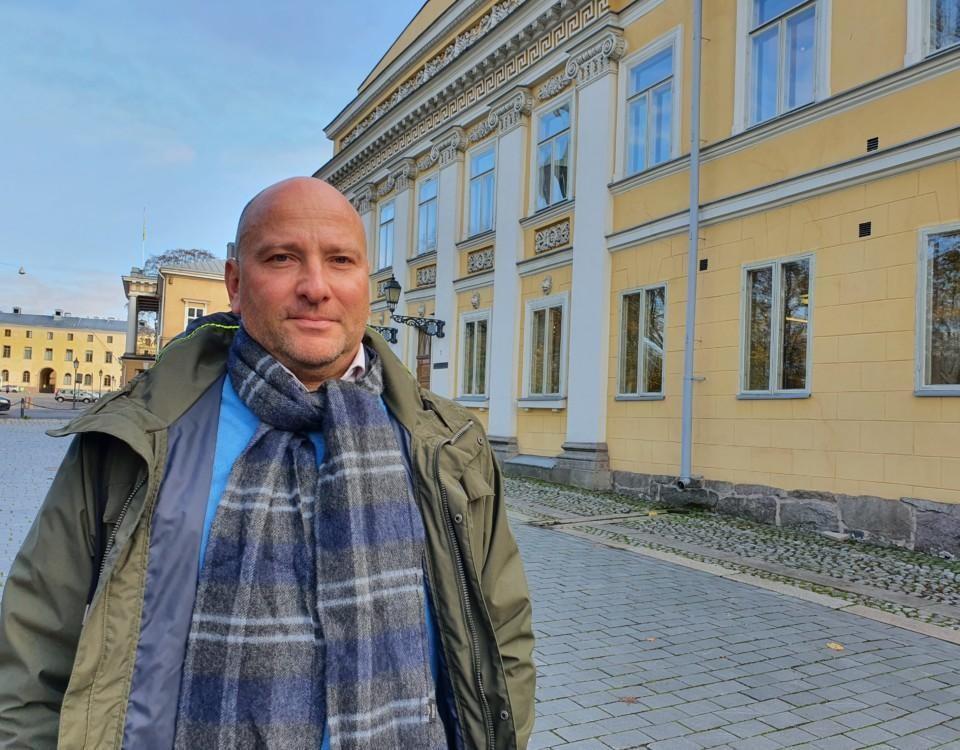 medelålders man utan hår står framför 1700-talsbyggnad vid Åbos gamla stortorg