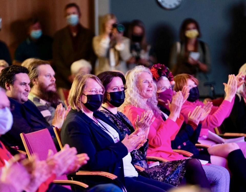Människor som publik i en sal. Presidenten fru på första raden.