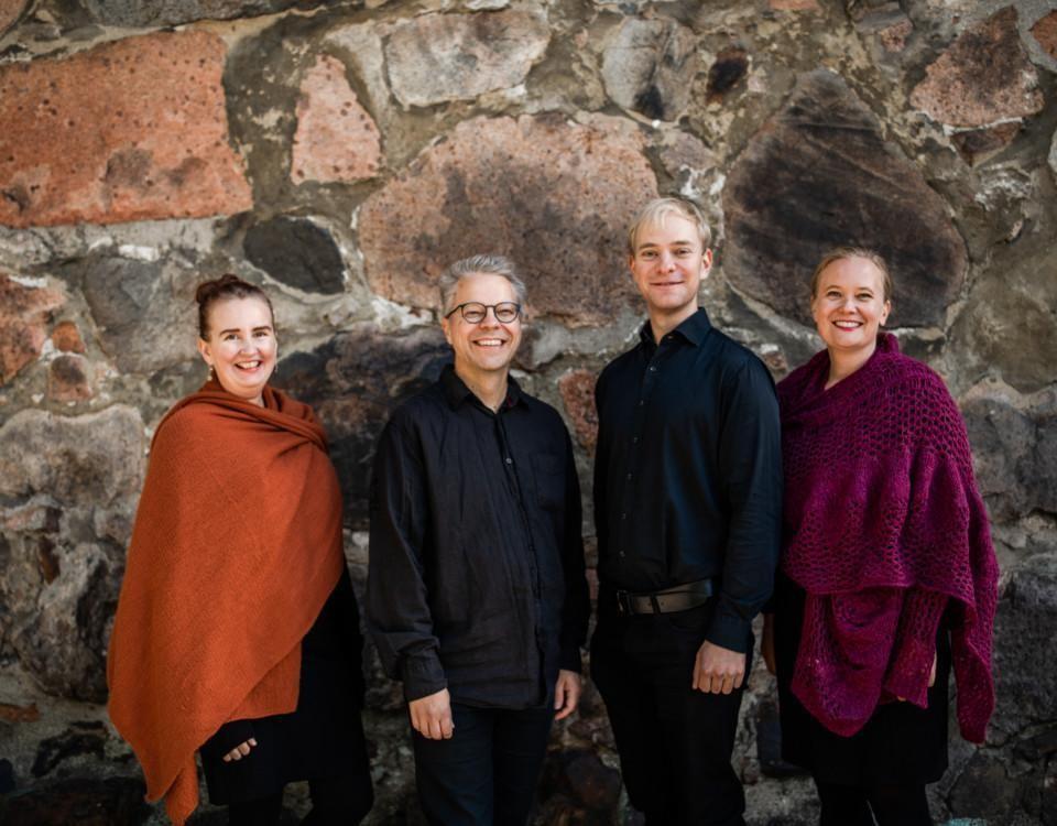 fyra personer står i rad framför domkyrkans vägg