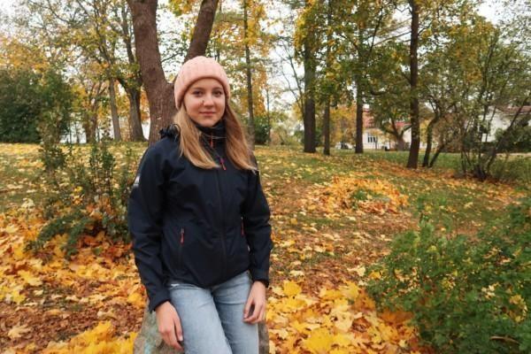 Bild av flicka som står lutad mot en stenpelare. I bakgrunden färggranna höstlöv.