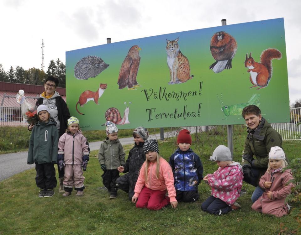 Välkomstskylt med djur samt en barngrupp utomhus